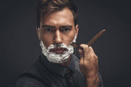 Foto de Hombre guapo joven con crema de afeitar en la cara, arreglarse la barba con navaja de afeitar y mirando a cámara - Imagen libre de derechos