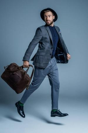 man in suit walking with leather bag