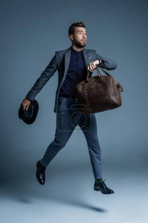Worried man walking with leather bag