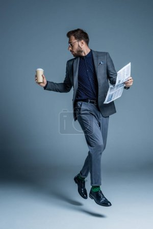 Businessman walking with coffee and newspaper