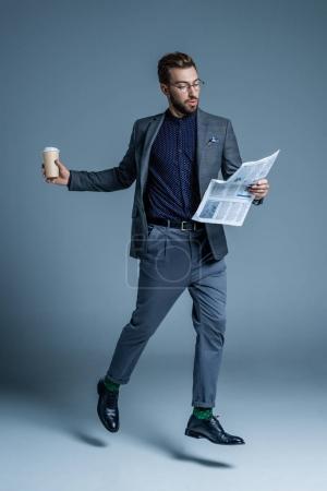 Photo pour Jeune bel homme en costume et verres à pied avec la tasse de café et le journal dans ses mains - image libre de droit