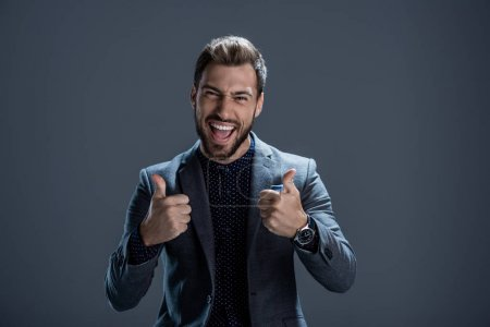 Photo for Excited young man in formal suit showing thumbs up and looking at camera - Royalty Free Image