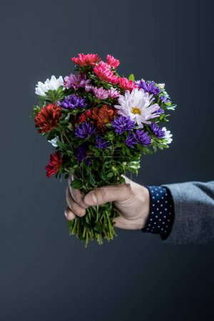 Photo for Cropped shot of man in suit holding a beautiful bouquet of colorful flowers - Royalty Free Image