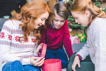 mother and kids opening christmas gift