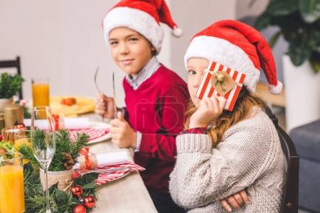 brother and sister sitting at christmas table