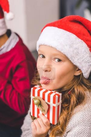 Girl with christmas gift showing tongue
