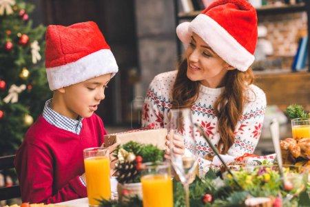 Photo pour Belle jeune mère donnant cadeau de Noël à son fils excité - image libre de droit