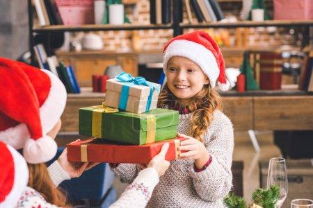 Photo pour Heureuse petite fille donnant pile de cadeaux à jeune mère - image libre de droit