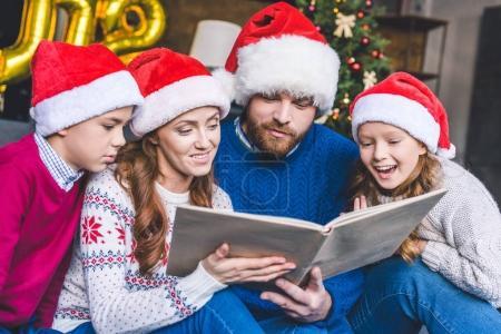 Family in santa hats reading book