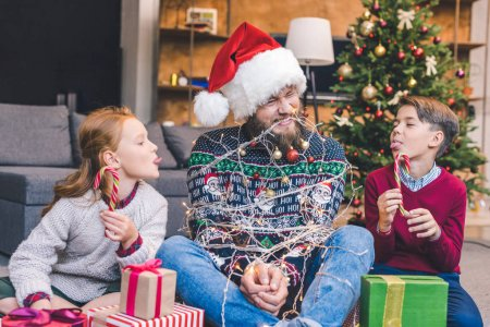 Kids and father tied up with garland