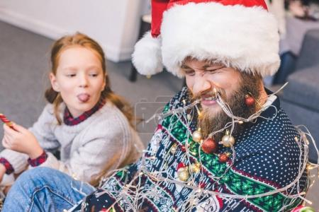 daughter and father tied up with garland