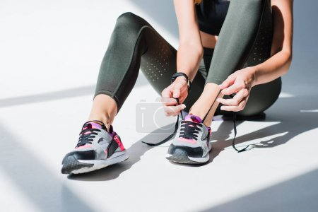 sportswoman tying shoelaces
