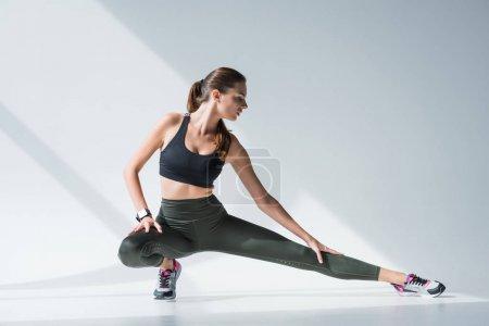 Photo pour Attrayant jeune femme en vêtements de sport étirement des muscles avant l'entraînement sur gris - image libre de droit