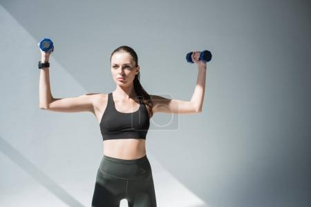 Photo for Sporty young woman training with dumbbells on grey - Royalty Free Image