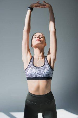 Photo pour Jeune femme athlétique avec les yeux fermés étirant les mains avant l'entraînement sur gris - image libre de droit