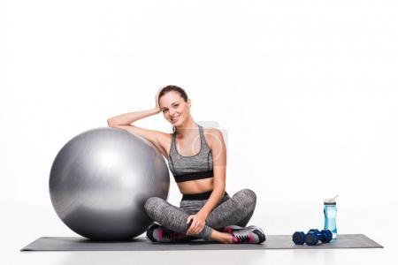 Photo pour Jolie fille sportive heureuse assis avec boule de remise en forme et souriant à la caméra isolé sur blanc - image libre de droit