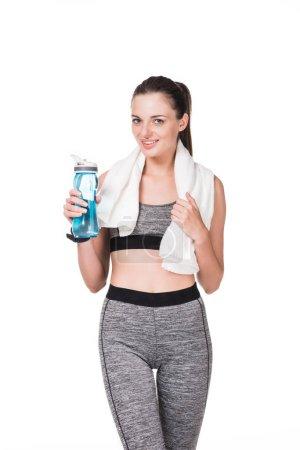 Photo pour Belle jeune sportive avec une serviette et bouteille d'eau, souriant à la caméra isolé sur blanc - image libre de droit