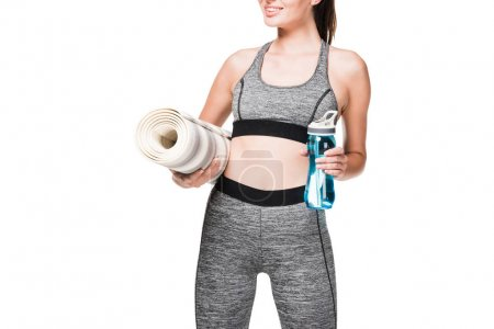 sportswoman with yoga mat and bottle of water