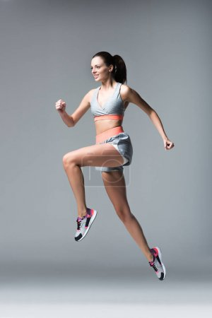 Photo for Full length view of smiling young woman running isolated on grey - Royalty Free Image