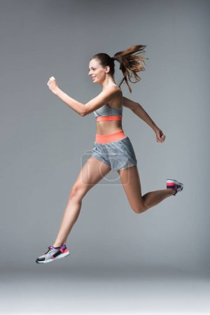 Photo for Smiling young sportswoman jogging and looking away isolated on grey - Royalty Free Image