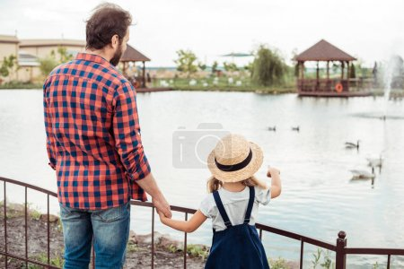 family looking at pond in park