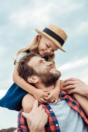 Photo for Little girl hugging happy father while piggybacking together - Royalty Free Image
