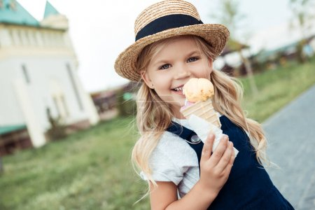 Photo for Portrait of smiling little girl with ice cream in hand looking at camera - Royalty Free Image