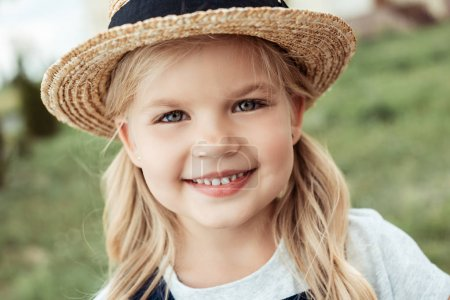Photo for Portrait of cheerful little caucasian girl in straw hat looking at camera - Royalty Free Image