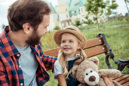 Photo for Father looking at little daughter while resting on bench together - Royalty Free Image