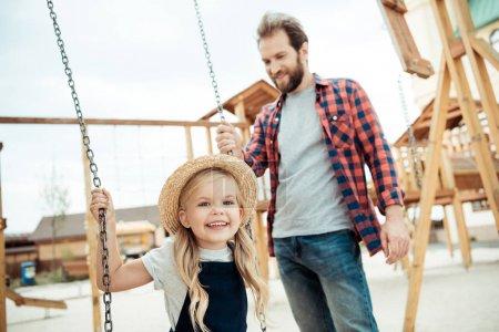 child swinging on swing