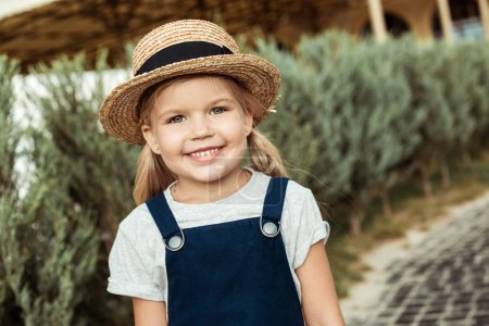 Photo for Portrait of smiling caucasian girl in straw hat looking at camera in park - Royalty Free Image