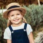 Portrait of smiling caucasian girl in straw hat lo...