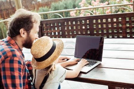 Photo pour Vue arrière du père et de la fille en utilisant l'ordinateur portable ensemble - image libre de droit