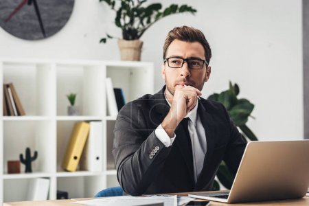 Photo for Thoughtful young businessman at workplace working with laptop - Royalty Free Image