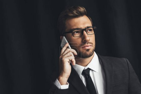 Photo for Handsome businessman in eyeglasses talking by phone isolated on black - Royalty Free Image