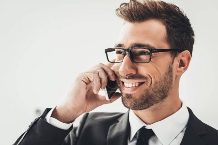 Photo for Close-up portrait of young happy businessman talking by phone - Royalty Free Image