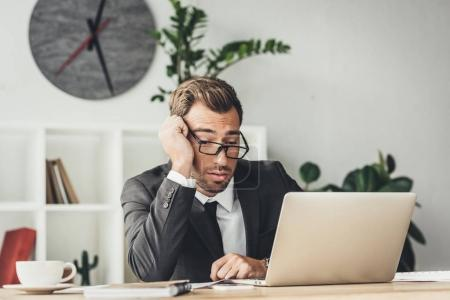 Exhausted businessman working with laptop