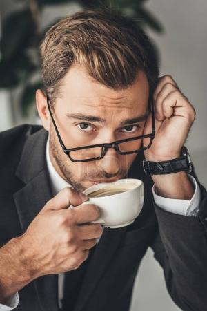 Photo for Close-up portrait of overworked businessman in eyeglasses drinking coffee - Royalty Free Image
