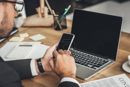 Photo pour Recadrée tir d'homme d'affaires à l'aide de smartphone sur lieu de travail - image libre de droit