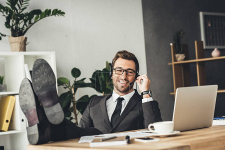 Photo for Handsome young call center worker with legs on table - Royalty Free Image