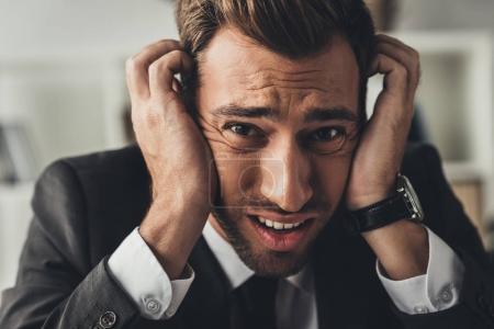 depressed businessman holding head