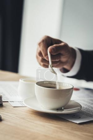 Businessman adding sugar to coffee