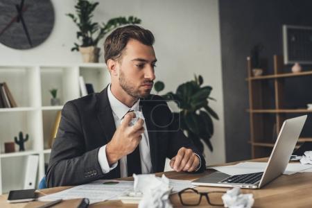 Photo pour Jeune homme d'affaires avec des papiers froissés sur table de travail - image libre de droit