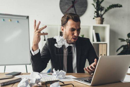Photo for Angry businessman throwing crumpled papers at modern office - Royalty Free Image