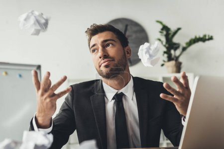 Photo for Young thoughtful businessman throwing crumpled papers at modern office - Royalty Free Image