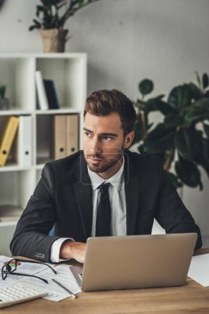 Gentil homme d'affaires avec ordinateur portable