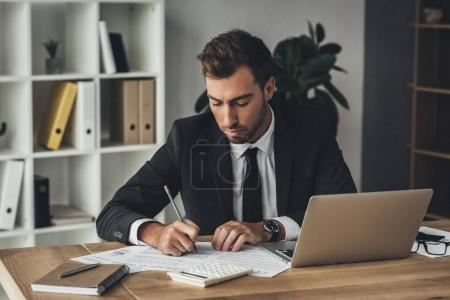 Photo for Young handsome businessman doing paperwork in modern office - Royalty Free Image