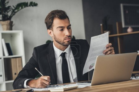 Photo for Handsome young businessman working with documents - Royalty Free Image