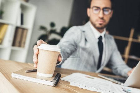Photo for Close-up shot of young businessman taking disposable cup of coffee from desk - Royalty Free Image