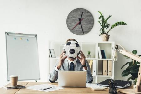 Businessman covering face with soccer ball